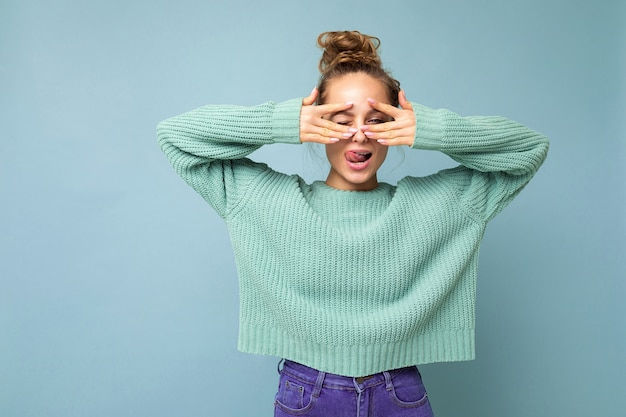 Foto einer jungen, positiven, fröhlichen, schönen blonden dame mit aufrichtigen emotionen, die einen lässigen blauen pullover trägt, der auf blauem hintergrund mit kopierraum isoliert ist und die augen mit den händen bedeckt und spaß hat.
