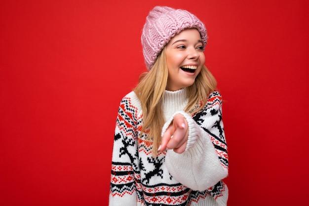 Foto einer jungen, positiven, fröhlichen, schönen blonden dame mit aufrichtigen emotionen, die rosa strickmütze und winterpullover trägt, einzeln auf rotem hintergrund mit leerem raum und auf die kamera gerichtet
