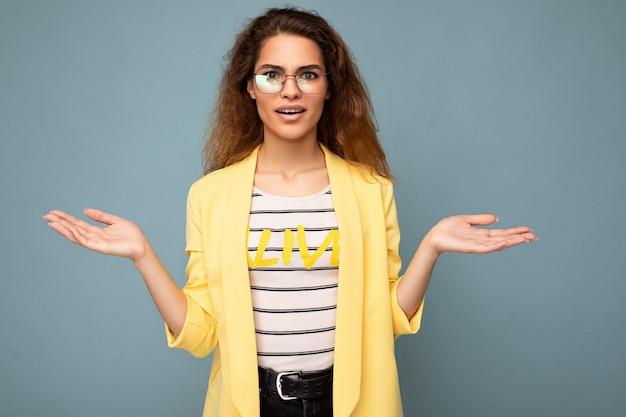 Foto einer jungen, positiven, nachdenklichen, schönen brünetten, lockigen frau mit aufrichtigen emotionen, die trägt
