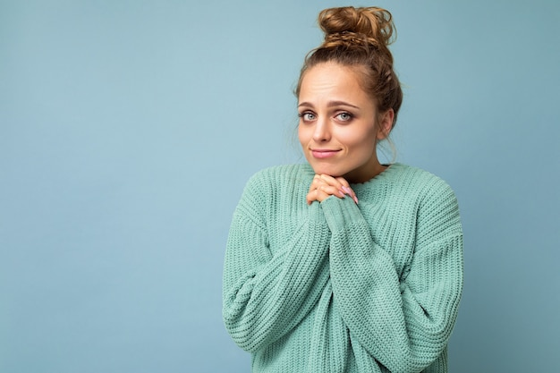 Foto einer jungen positiven schönen blonden frau mit aufrichtigen emotionen, die einen lässigen blauen pullover trägt