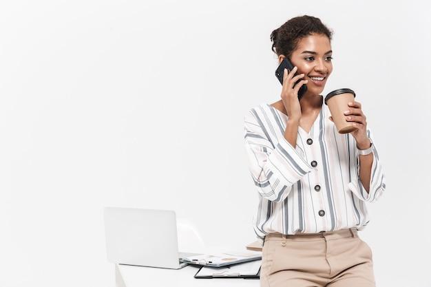 Foto einer jungen schönen afrikanischen frau, die lokalisiert über der weißen wand aufwirft, die durch trinkenden kaffee des handys spricht.