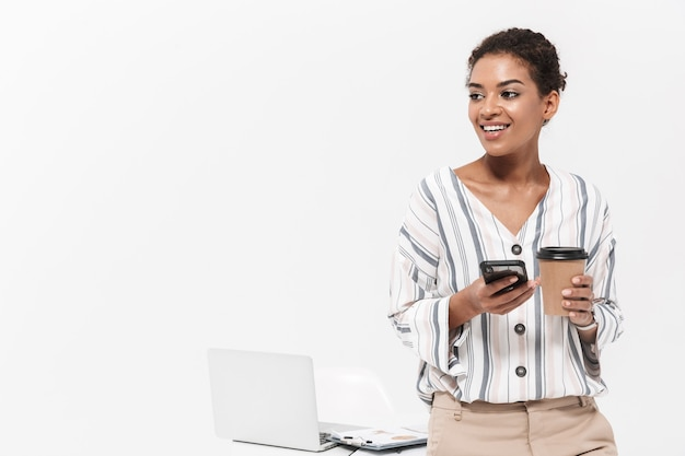 Foto einer jungen schönen afrikanischen frau posiert isoliert über weiße wand mit handy trinken kaffee.