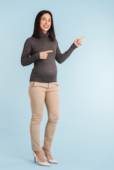 Foto einer jungen schwangeren frau lokalisiert auf copyspace zeigend.