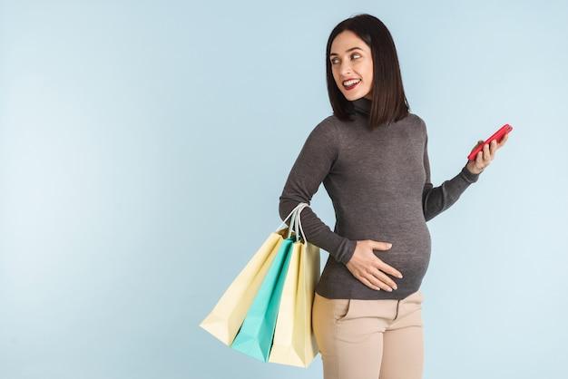 Foto einer jungen schwangeren frau lokalisiert unter verwendung des handys, das einkaufstaschen hält.