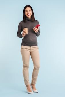 Foto einer jungen schwangeren frau lokalisiert unter verwendung des mobiltelefons.