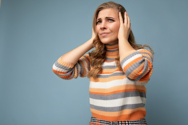Foto einer jungen unzufriedenen, attraktiven blonden, lockigen frau mit aufrichtigen emotionen, die einen lässigen gestreiften pullover trägt, der auf blauem hintergrund mit kopienraum isoliert ist und die ohren bedeckt, die versuchen, nicht zu hören.