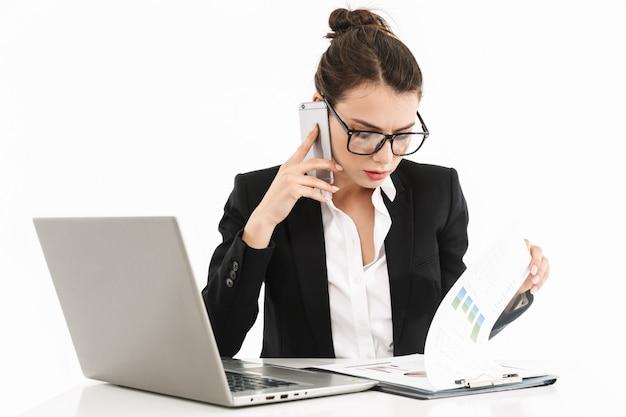 Foto einer kaukasischen arbeiterin in formeller kleidung, die am schreibtisch sitzt und am laptop im büro arbeitet, isoliert über weißer wand