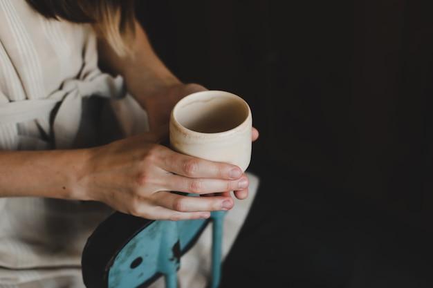 Foto einer keramiktasse in weiblichen händen nahaufnahme