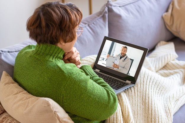 Foto einer kranken älteren frau zu hause während der online-cousultation mit einem arzt. gesundheitskonzept.
