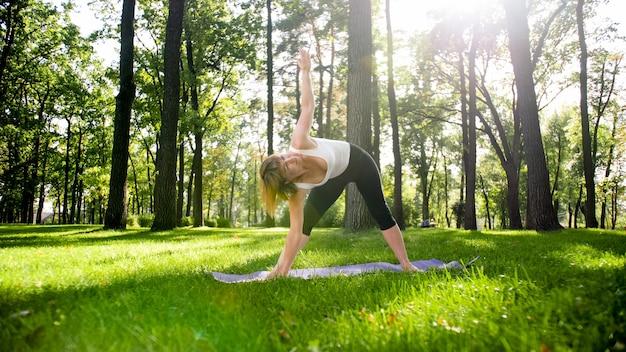 Foto einer lächelnden frau mittleren alters, die yoga praktiziert und im park meditiert. frau streckt sich und macht fitness auf der matte im wald