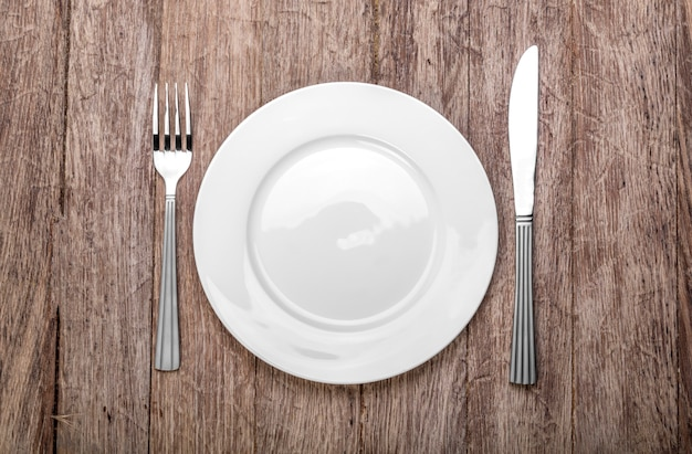 Foto einer leeren weißen platte mit messer und gabel auf einem rustikalen holztisch