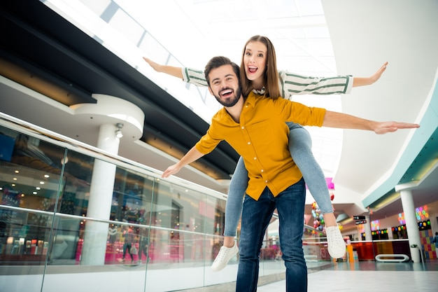 Foto einer lustigen dame, die arme wie flügel ausbreitet, gut aussehender kerl, der ihr huckepack trägt, um das einkaufszentrum zu besuchen, zusammen paar gute laune, die spaß hat, abenteuer zu treffen, lässiges outfit drinnen tragen