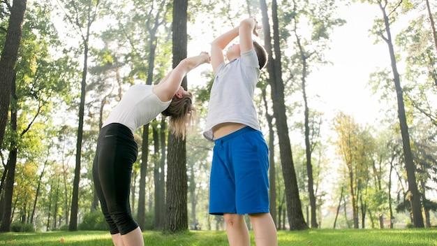 Foto einer mutter mittleren alters mit ihrem kind im teenageralter, die yoga und atemübungen im park macht. familie, die sich beim sport um ihre geistige und körperliche gesundheit kümmert