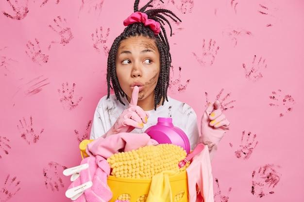 Foto einer mysteriösen dunkelhäutigen ethnischen frau macht eine geheime geste, drückt den zeigefinger auf die lippen und posiert in der nähe eines korbes voller wäsche und chemischer reinigungsmittel, isoliert über schmutziger rosa wand isolated