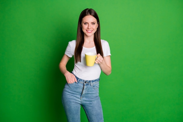 Foto einer optimistischen, netten, brünetten dame, die einen becherständer trägt, trägt weiße t-shirt-jeans einzeln auf grünem hintergrund
