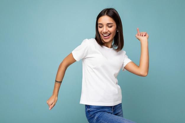 Foto einer positiv lächelnden jungen schönen brünetten frau mit aufrichtigen emotionen, die ein lässiges weißes t-shirt für das modell trägt, isoliert auf blauem hintergrund mit kopienraum und tanz.