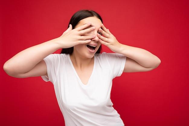 Foto einer positiven jungen schönen brünetten frau mit aufrichtigen emotionen, die ein weißes t-shirt für das modell trägt, isoliert auf rotem hintergrund mit leerem raum und bedeckt die augen.