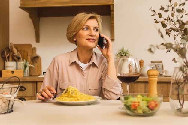 Foto einer reifen positiven seniorin, die zu hause in der küche mit handy sitzt.