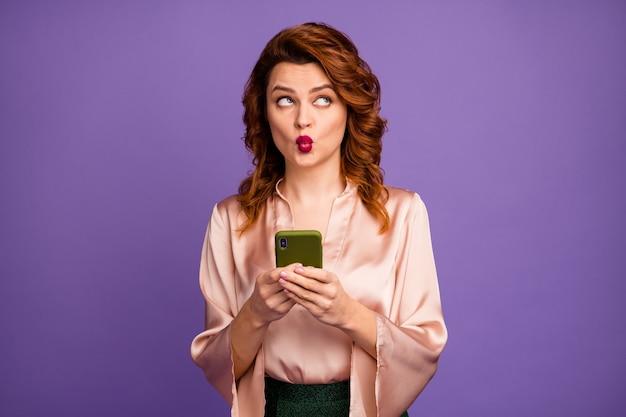 Foto einer schicken dame, die das telefon mit der seite nach oben in den leeren raum hält