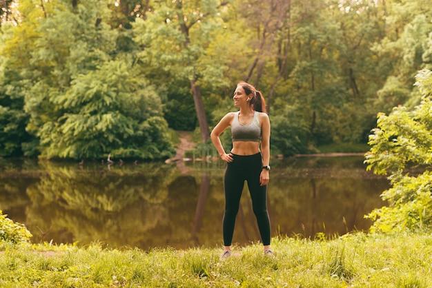 Foto einer schlanken jungen sportfrau, die bei sonnenuntergang in der nähe eines sees im park steht?