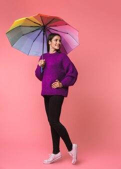 Foto einer schönen emotionalen jungen frau, die lokal über rosa raum hält, der regenbogenregenschirm hält.