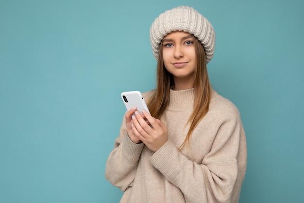 Foto einer schönen ernsten jungen blonden frau, die einen stilvollen beige warmen pullover und einen gestrickten winter trägt
