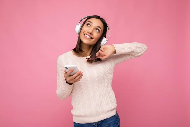 Foto einer schönen fröhlich lächelnden jungen frau, die stilvolle freizeitkleidung trägt, die über der hintergrundwand isoliert ist und ein mobiltelefon mit weißen bluetooth-kopfhörern trägt und musik hört und havi