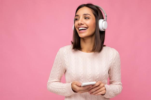 Foto einer schönen, fröhlich lächelnden jungen frau, die stilvolle freizeitkleidung trägt, die über isoliert ist