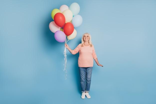 Foto einer schönen gastfrau, die luftballons in rosa pullover auf blauem hintergrund hält