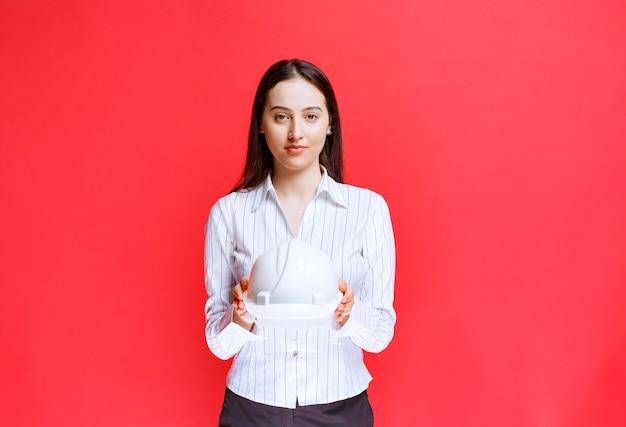Foto einer schönen geschäftsfrau, die sicherheitshut auf roter wand hält.