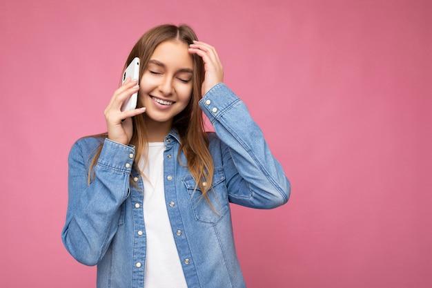 Foto einer schönen glücklich lächelnden jungen blonden frau, die ein lässiges blaues jeanshemd trägt, isoliert auf rosa hintergrund, das in der hand hält und mit geschlossenen augen auf dem handy spricht