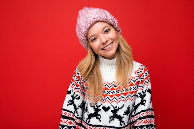 Foto einer schönen glücklich lächelnden jungen blonden frau, die über roter hintergrundwand isoliert ist und einen winterpullover und einen trendigen rosa hut mit blick auf die kamera trägt.