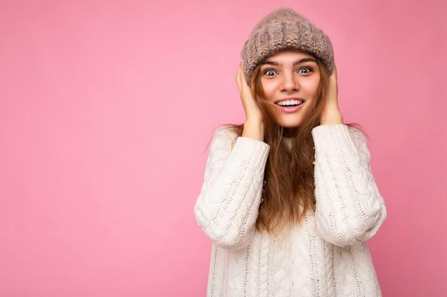 Foto einer schönen, glücklich lächelnden jungen brünetten frau, die über rosafarbener hintergrundwand isoliert ist