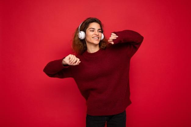 Foto einer schönen glücklich lächelnden jungen brünetten lockigen frau, die einen dunkelroten pullover trägt, isoliert über