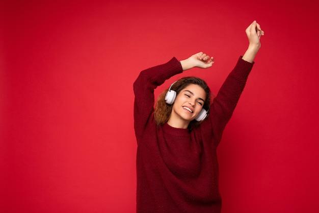Foto einer schönen, glücklich lächelnden jungen, brünetten, lockigen frau, die einen dunkelroten pullover trägt, isoliert über