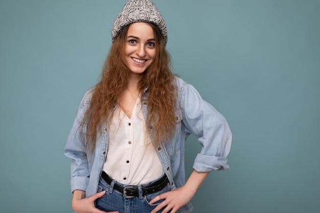 Foto einer schönen, glücklich lächelnden jungen dunkelblonden, lockigen frau, die isoliert über der blauen hintergrundwand steht und weißes hemd mit jeanshemd und grauem hut trägt und in die kamera schaut.