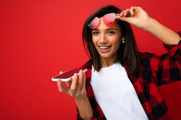 Foto einer schönen glücklichen, fröhlichen jungen brunet-frau, die ein stylisches rotes hemd trägt, ein weißes t-shirt und eine rote sonnenbrille, die auf rotem hintergrund isoliert ist und eine sprachnachricht mit dem handy aufzeichnet, die in die kamera schaut.