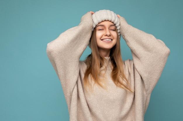 Foto einer schönen glücklichen, fröhlichen jungen dunkelblonden weiblichen person, die über blauer hintergrundwand isoliert ist und beige warmer pullover und gestrickte beige mütze trägt, die mit engen augen genießt. platz kopieren