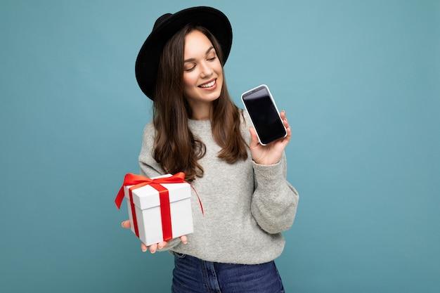 Foto einer schönen glücklichen, fröhlichen jungen frau, die auf blauem hintergrund isoliert ist und schwarz trägt