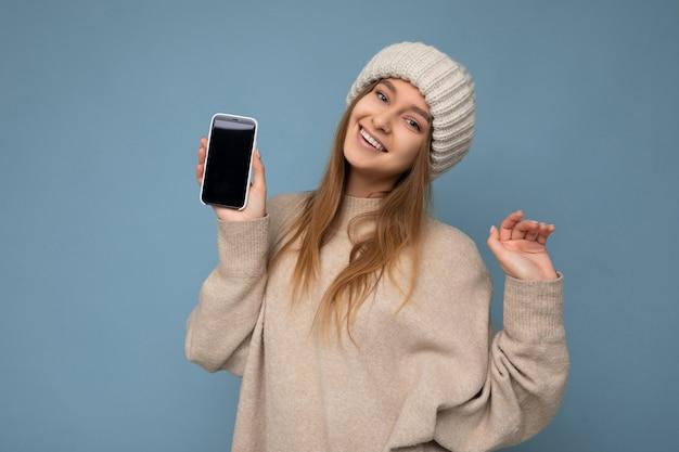 Foto einer schönen, gut aussehenden jungen frau, die einen stylischen beige pullover und beige gestrickt trägt