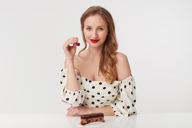 Foto einer schönen jungen blondine mit roten lippen in einem gepunkteten kleid. mit einem kuchen am tisch sitzen und eine kirsche in den händen halten. lächeln isoliert über weißem hintergrund.
