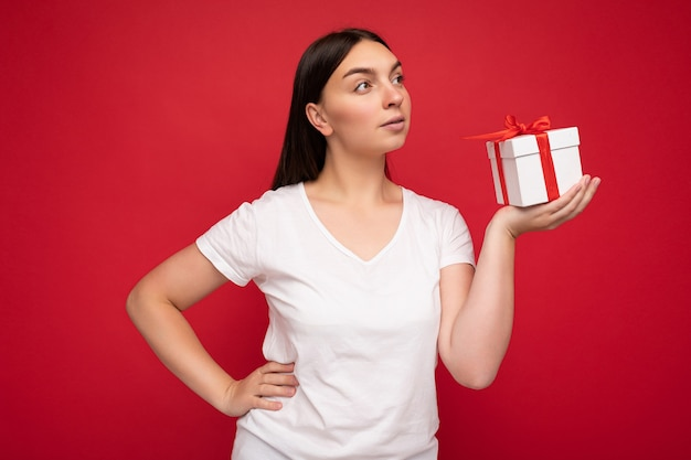 Foto einer schönen jungen brünetten frau, die über einer roten hintergrundwand isoliert ist und ein weißes, lässiges t-shirt für ein modell trägt, das eine weiße geschenkbox mit rotem band hält und zur seite schaut