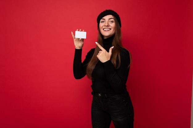 Foto einer schönen jungen brünetten frau mit schwarzem pullover und hut isoliert auf rotem hintergrund, die kreditkarte in die kamera schaut und mit dem finger auf die plastikkarte zeigt