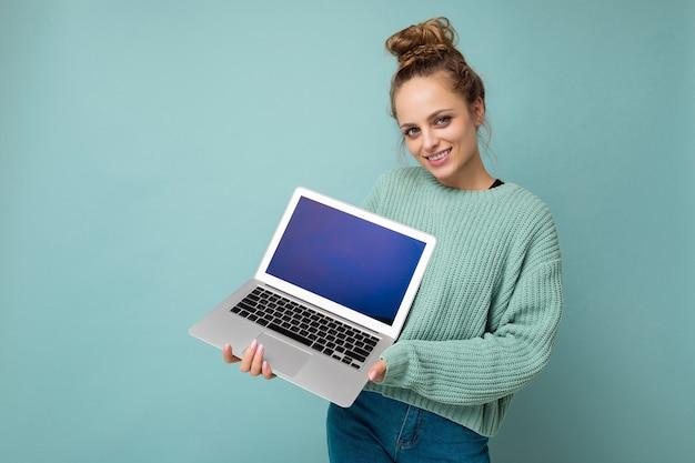 Foto einer schönen jungen frau, die einen computer-laptop hält und in die kamera schaut, die über buntem hintergrund isoliert ist?