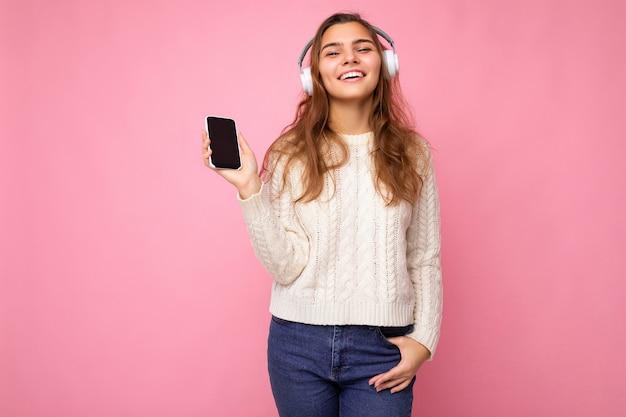 Foto einer schönen jungen frau, die einen hellweißen, stylischen pullover trägt, isoliert auf rosa hintergrund