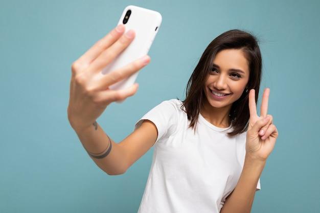 Foto einer schönen lächelnden, glücklichen jungen brünetten frau, die ein lässiges weißes t-shirt trägt, das über der wand isoliert ist?