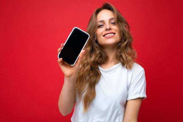Foto einer schönen lächelnden jungen blonden frau, die gut aussieht und ein weißes t-shirt trägt, das isoliert auf rotem hintergrund steht, mit kopienraum, der das telefon hält und das smartphone in der hand mit leerem bildschirm zeigt