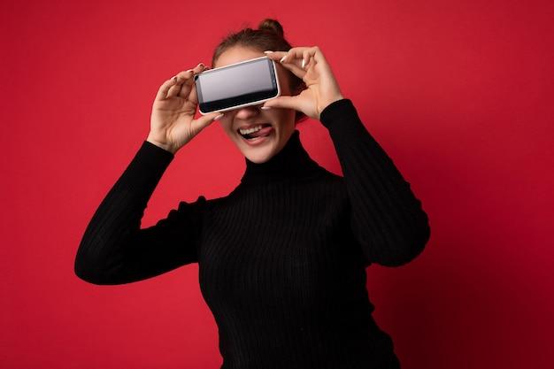 Foto einer schönen lächelnden jungen brünetten frau, die einen schwarzen pullover trägt, der isoliert auf rotem hintergrund steht und ein mobiltelefon mit leerem bildschirm für mockup zeigt und zunge zeigt
