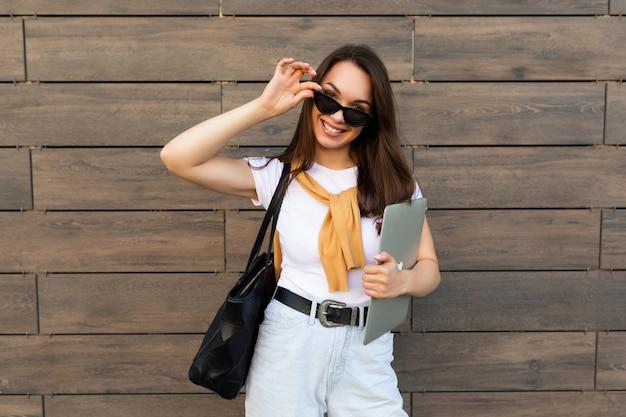 Foto einer schönen lächelnden jungen dame mit weißem t-shirt, hellblauen jeans und gelbem pullover mit computer-laptop und schwarzer sonnenbrille, die auf der straße bleibt und in die kamera schaut