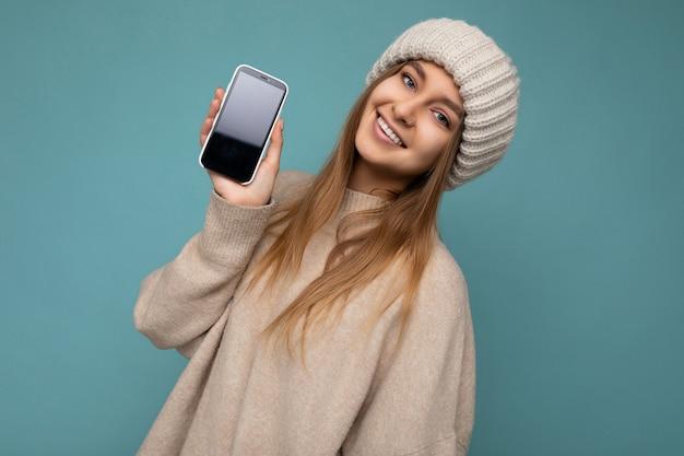 Foto einer schönen lächelnden jungen frau, die gut aussieht und ein lässiges, stilvolles outfit trägt, das isoliert steht